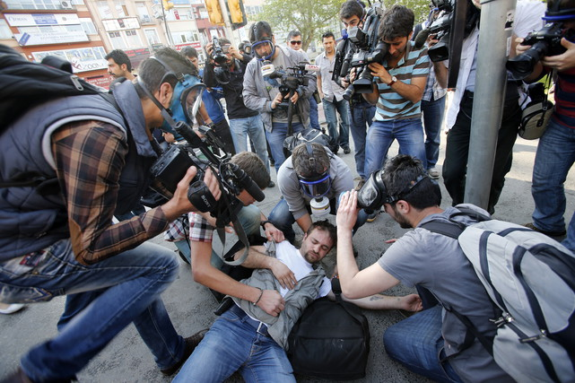 An injured journalist is filmed and helped by his colleagues during clashes between riot police and May Day protesters in central Istanbul May 2013.