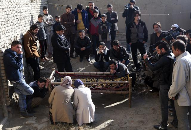 Colleagues and friends of Afghan video journalist Zubair Hatami, who died from injuries sustained in a Taliban attack, mourn over his coffin during his funeral, in Kabul, Afghanistan, Dec. 21, 2014.