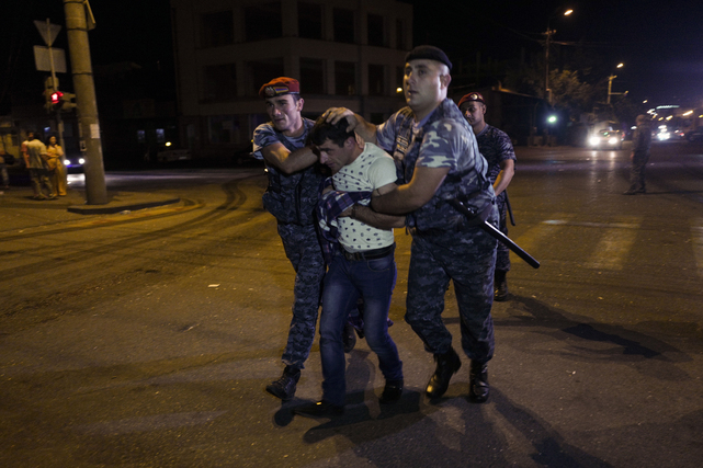 Police officers detain a supporter of the armed group who have been holding a police station in Yerevan, Armenia, 27 July 2016.