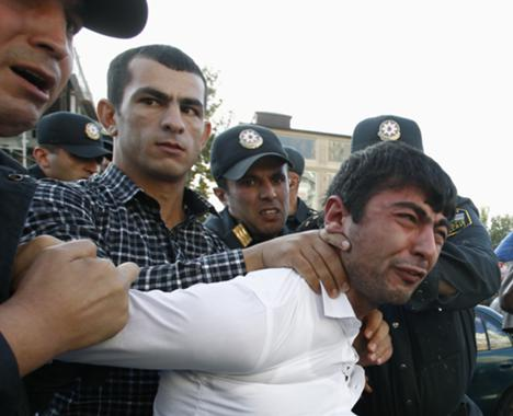 Police detain an opposition supporter in Baku, 12 October 2013