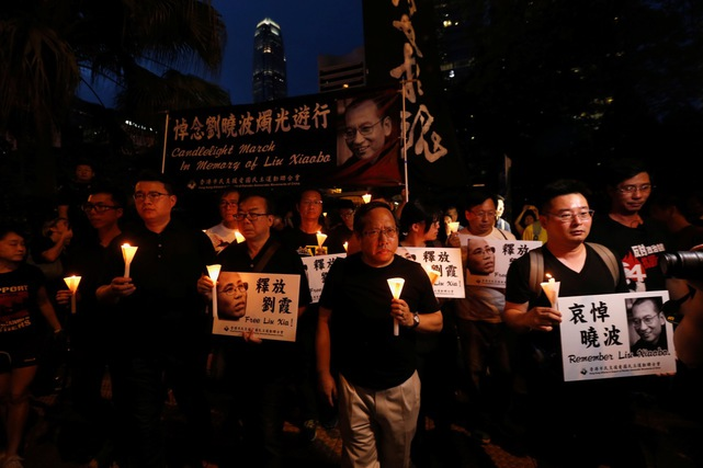 Protesters carrying candles take part in a march to mourn the death of Nobel Peace laureate Liu Xiaobo, in Hong Kong, China, 15 July 2017