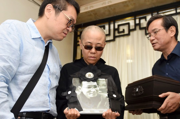 Liu Xia, center, holds a portrait of him during his funeral in Shenyang in northeastern China's, 15 July 2017. The photo shows, from left to right, Liu Hui, younger brother of Liu Xia, Liu Xia and Liu Xiaoxuan, younger brother of Liu Xiaobo holding his cremated remains