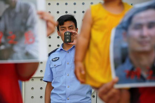 A police officer films family members of those detained in what is known as the