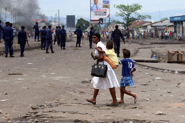 A family pass near Congolese riot police during a protest in Kinshasa, 19 September 2016