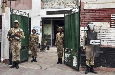 Egyptian soldiers stand guard in the courtyard of a school that will be used as a polling station in downtown Cairo on 13 January 2014