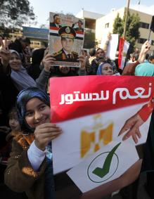 Egyptian women supporting the army hold a poster showing a