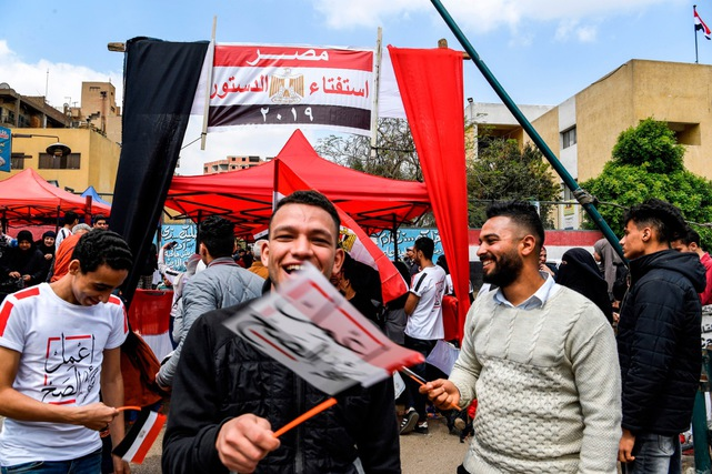 Egyptian youth wave miniature flags that read