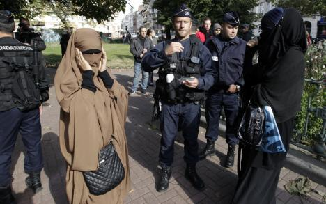 French police and gendarmes check identity cards of two women for wearing full-face veils, or niqabs, in Lille, 22 September 2012.