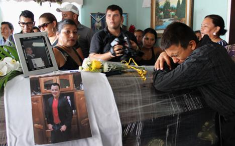 A relative of slain television journalist Herlyn Espinal mourns over his coffin during a wake at his home in Santa Rita municipality, in the outskirts of San Pedro Sula July 22, 2014.