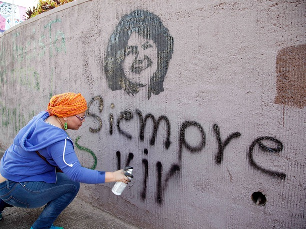 A woman spray paints the phrase
