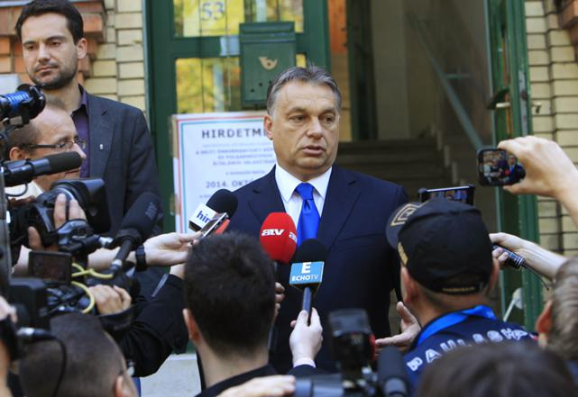 Hungary's Prime Minister Viktor Orban talks to journalists after casting his vote during Hungary's municipal elections in Budapest, October 12, 2014