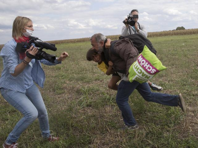 A migrant runs with a child before being tripped by TV camerawoman Petra Laszlo (L) and falling as he tries to escape from a collection point in Roszke village, Hungary, 8 September 2015.