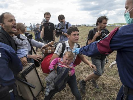 A migrant carrying a baby is stopped by Hungarian police officers as he tries to escape on a field nearby a collection point in the village of Roszke, Hungary, 8 September 2015