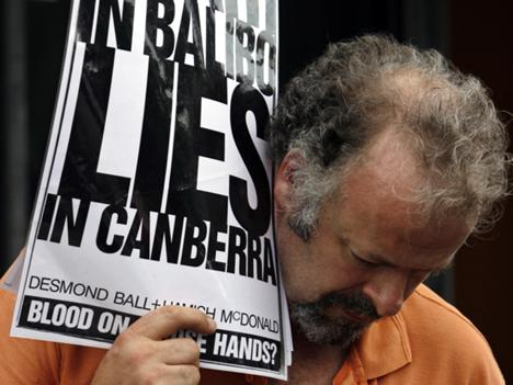 In this 8 May 2007 file photo, a protester holds a placard outside the Glebe Coroner's Court in Sydney during the inquest into Brian Peters' death