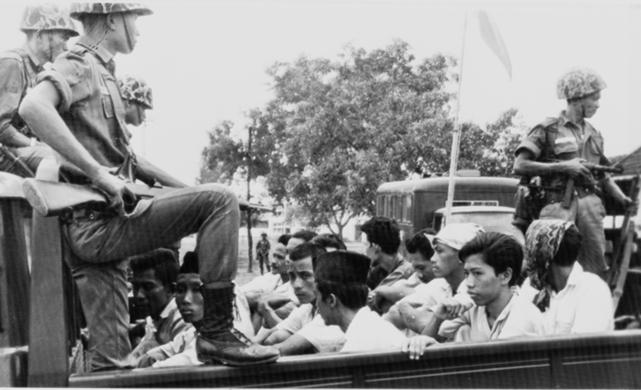In this 30 October 1965 file photo, members of the Youth Wing of the Indonesian Communist Party are guarded by soldiers as they are being taken to prison in Jakarta