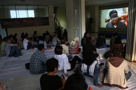 In this 30 September 2013 photo, people watch the documentary film