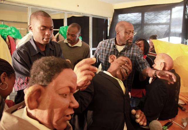 Godfrey Gado Mwampembwa (right), prepares for the XYZ show - a satirical puppet show that he created - at his studio in Nairobi, 21 May 2009.