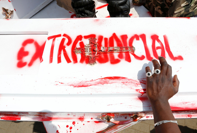 A member of the civil society holds a coffin stained with mock blood as others chant slogans, during a protest dubbed