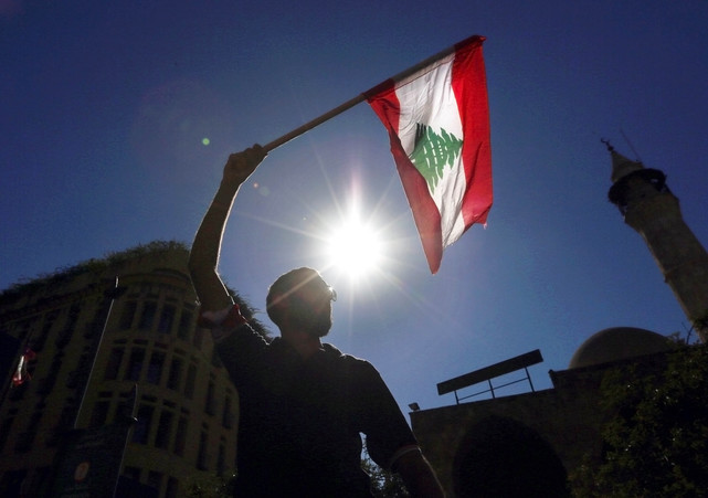 Man waves a Lebanese flag during a protest near the parliament building in downtown Beirut, Lebanon