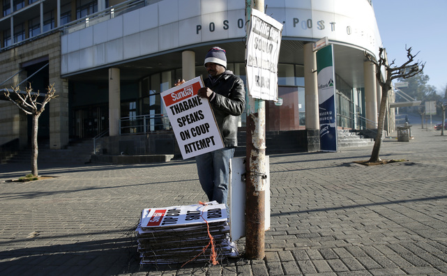A worker hangs posters displaying newspaper headlines, in Maseru, Lesotho, 31 August 2014