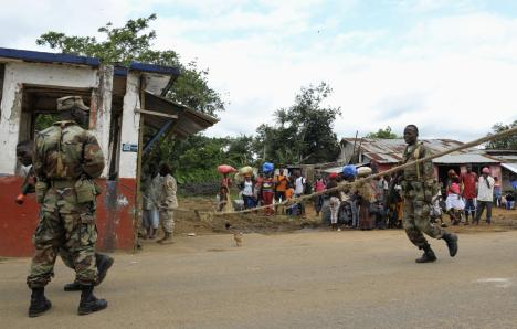 Liberian soldiers check people travelling in Bomi County, 11 August 2014. Liberian troops set up Ebola roadblocks and stopped public access to some of the worst-hit towns after the country declared a state of emergency