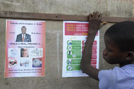 A boy stands near posters displaying a government message against Ebola at Duwala market in Monrovia, 17 August 2014