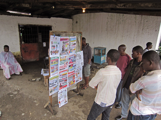 People read local newspaper headlines in Monrovia, Liberia, 31 July 2014