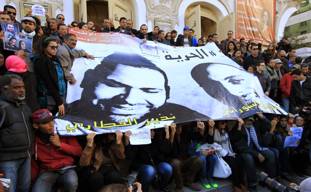 People pose around a poster of journalists Nadhir Ktari (L, in poster) and Sofiane Chourabi, who went missing in Libya in September, during a demonstration over their disappearance, in Tunis January 9, 2015