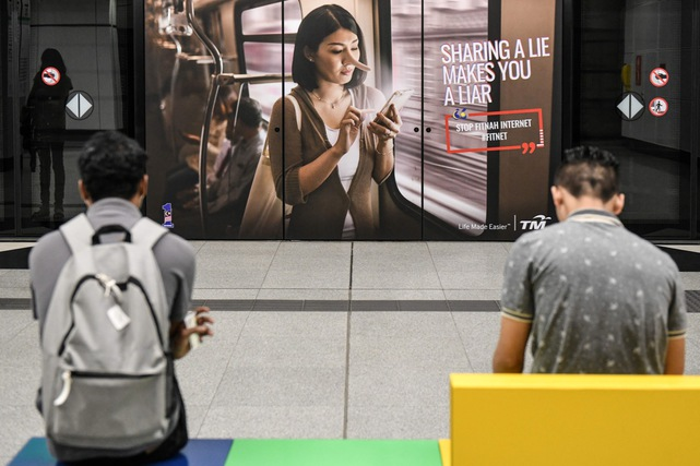 Commuters wait for the train in front of a government advertisement about 'fake news', at a station in Kuala Lumpur, Malaysia, 26 March 2018