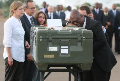 Serge Daniel, right, correspondent for Radio France Internationale, weeps at the coffin of one of the two French journalists executed in Mali, 4 November 2013.