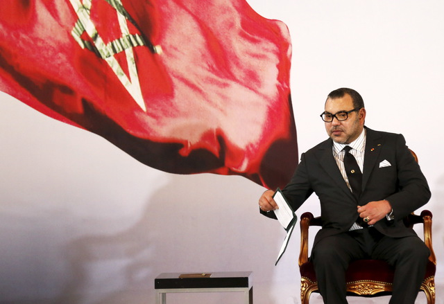Morocco's King Mohammed VI holds a book during a visit, at the presidential palace in Abidjan June 2, 2015