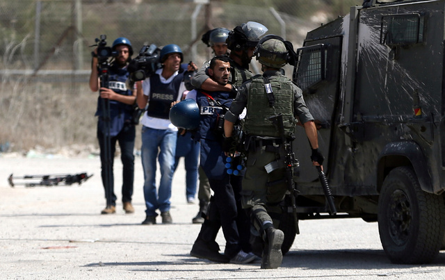 Israeli border policemen detain a Palestinian journalist during clashes with Palestinian protesters near Israel's Ofer Prison near the West Bank city of Ramallah August 3, 2016.