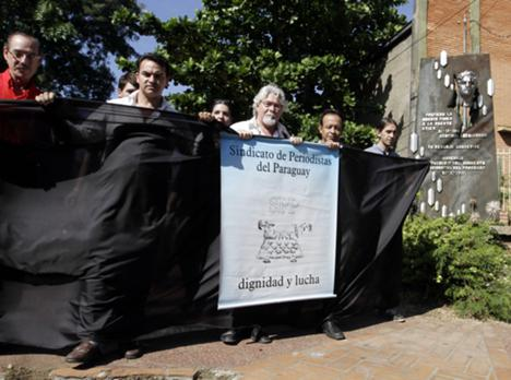 Journalists demonstrate on Paraguayan Journalist Day in 2013 beside a memorial commemorating the death of journalist Santiago Leguizamon