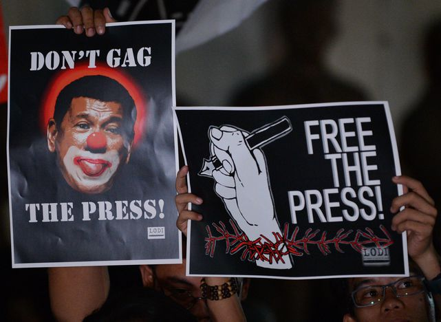 Journalists and supporters display placards showing President Rodrigo Duterte as a clown during a protest in support of Rappler Manila on January 19, 2018