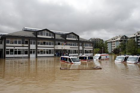 Ambulances are seen half submerged in floodwaters in front of a school in the flooded town of Obrenovac, Serbia