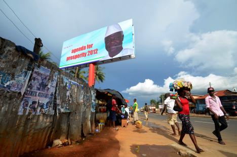 People walk past a campaign poster for President Ernest Bai Koroma. Two Sierra Leonean editors are currently facing charges for