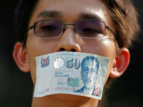 A man covers his mouth with a Singaporean 50 dollar note (US$40) during a protest in Singapore against new licensing regulations imposed by the government for online news sites, 8 June 2013