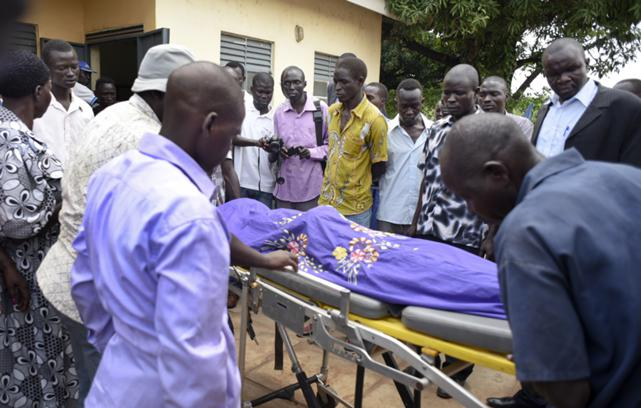 Mourners watch as the body of South Sudanese journalist Moi is taken into the mortuary in Juba, South Sudan, 20 August 2015