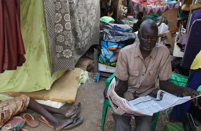A displaced man reads a newspaper at Tomping camp, in Juba, South Sudan, 10 January 2014