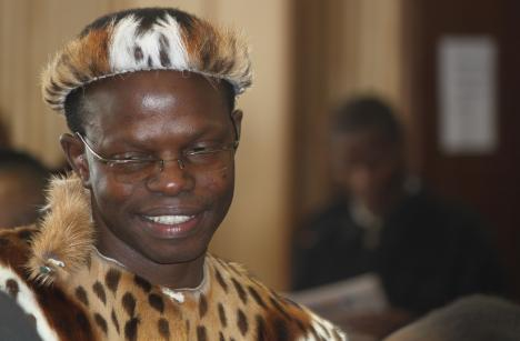 In this photo taken Wednesday, June 4, 2014, lawyer Thulani Maseko, appears in court in the traditional animal skin garb of a Zulu warrior, in Mbabane, Swaziland.