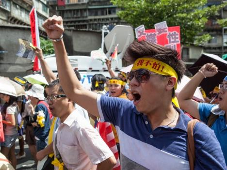 Activists and civic groups march in Taipei in protest against the Want Want China Times Group's planned acquisition of China Network Systems' cable TV services in September 2012