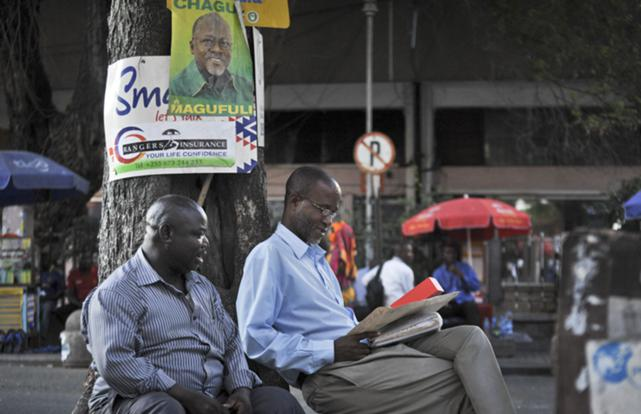 Tanzanians sit next to a tree, underneath an election poster for ruling party presidential candidate John Magufuli, as they await election results in Dar es Salaam, Tanzania 27 October 2015
