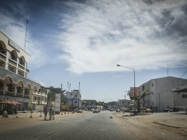 Residents walk on an empty street in Banjul, The Gambia, 30 December 2014