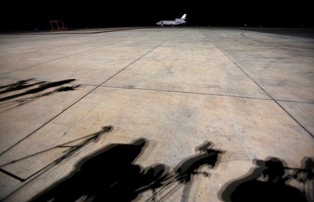 Journalists cast shadows as they await former Gambian President Yahya Jammeh's arrival at the airport of Banjul, Gambia, 21 January 2017