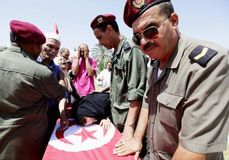 Family members and colleagues mourn near the coffin of Tunisian soldier Lamjid al-Arfaoui during his funeral