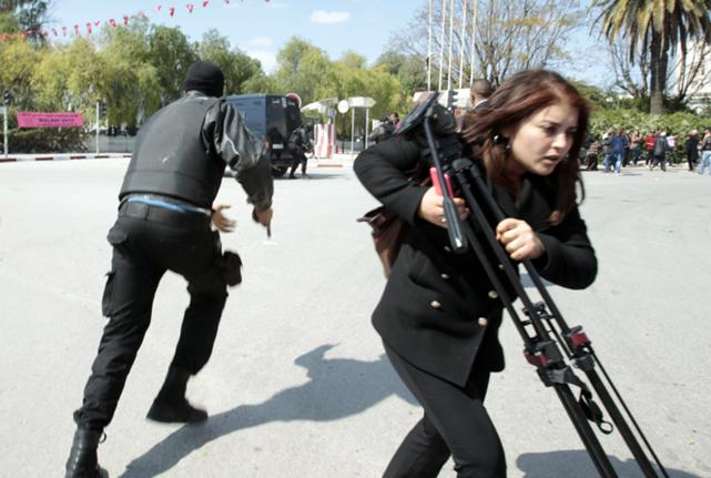Police officers and a journalist run outside the parliament in Tunis March 18, 2015 after gunmen in military uniforms stormed Tunisia's national museum