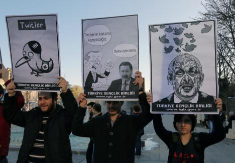 Members of the Turkish Youth Union hold cartoons depicting Turkey's Prime Minister Recep Tayyip Erdogan during a protest against a ban on Twitter, in Ankara, 21 March 2014.
