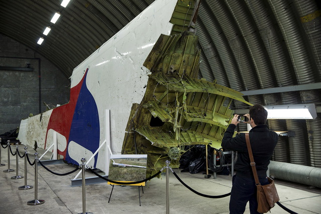 A journalist takes a picture of a piece of wreckage of the MH17 airplane after the presentation of the final report into the crash of July 2014 of Malaysia Airlines flight MH17 over Ukraine, in Gilze Rijen, the Netherlands, 13 October 2015