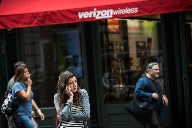 A woman uses her phone in front of a Verizon Store, one of several telecom companies police could force to disclose customer location and data under the Kelsey Smith Act, New York, United States, 2013