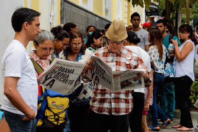 People read newspapers in a line up in Caracas, Venezuela, 19 March 2015